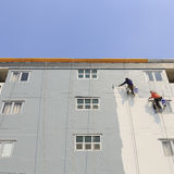 The painter uses a paint roller outside high building Stock Photos