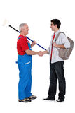 Decorator welcoming a new apprentice. Painter welcoming a new teenage apprentice Royalty Free Stock Photo