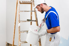 Painter in white dungarees, blue t-shirt Royalty Free Stock Photo
