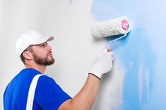 Painter in white dungarees, blue t-shirt. Portrait of handsome young painter in white dungarees, blue t-shirt, cap and gloves painting a wall with paint roller Royalty Free Stock Photos