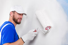 Painter in white dungarees, blue t-shirt. Portrait of handsome young painter in white dungarees, blue t-shirt, cap and gloves painting a wall with paint roller Stock Image