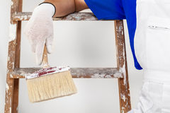 Painter in white dungarees, gloves and paint brush Royalty Free Stock Images