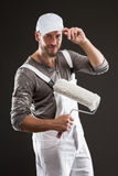 Painter in white dungarees and hat standing with paint roller Stock Image