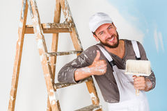 Painter in white dungarees with thumbs up gesture Royalty Free Stock Photography