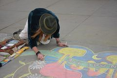Painter who draws with chalk on the ground in Trafalgar Square in London in May 2015 stock images