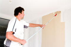 Painter at work. Using a roller brush Royalty Free Stock Photography