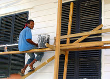 Painter at work. Black painter man sitting on scaffolding working on wooden house maintenance, Paramaribo, Suriname Stock Images
