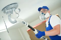 Painter work with ceiling. polishing and sanding the surface after putty for painting. Painter work with ceiling sander. polishing and sanding the surface after stock photography