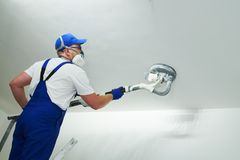 Painter work with ceiling. polishing and sanding the surface after putty for painting. Painter work with ceiling sander. polishing and sanding the surface after royalty free stock image