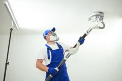Painter work with ceiling. polishing and sanding the surface after putty for painting. Painter work with ceiling sander. polishing and sanding the surface after royalty free stock photos