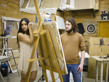 Painter at work with model muse in studio waiting inspiration Royalty Free Stock Photography