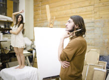Painter at work with model muse in studio waiting inspiration Stock Images