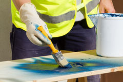 Painter. At work painting a wood Royalty Free Stock Photography