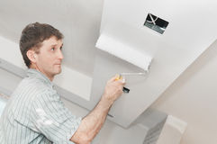 Painter worker painting a ceiling royalty free stock image