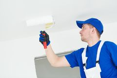 Painter painting ceiling with paint roller Royalty Free Stock Image