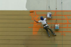 Painter. Worker is painting on old wall Royalty Free Stock Image