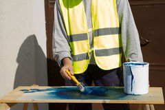 Painter. Worker painting a plank for a construction Stock Photo