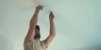 Painter working with paint roller and brushes to paint the room Royalty Free Stock Images