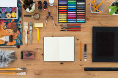 Painter workplace top view. Wooden table of an artist with art tools for drawing. Royalty Free Stock Image