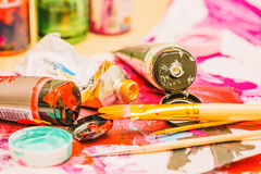 Painter workplace with tubes of multicolor oil paint and paintbrushes on painted paper close up Royalty Free Stock Images