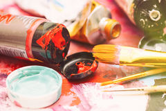 Painter workplace with tubes of multicolor oil paint and paintbrushes on painted paper close up with selective focus Stock Photo