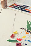 Painter workplace with watercolor pallete anr other tools Royalty Free Stock Image