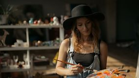 Painter Works with Palette. Happy caucasian painter works with palette and brushes, talented and intelligent woman conceiving image for the painting, working in stock footage