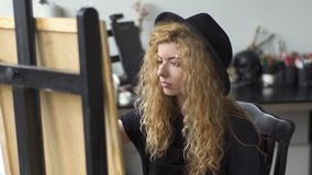 Painter works in studio. Attractive creative painter with long curly hair working at the easel in the studio, looking at the picture to figure out what to add to stock video
