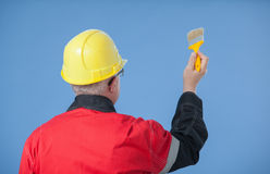 Painter in an yellow helmet holding a brush, rear view Royalty Free Stock Photo