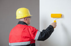Painter in an yellow helmet holding a roller Royalty Free Stock Image