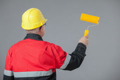 Painter in an yellow helmet holding a yellow roller Stock Photos