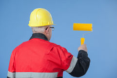 Painter in an yellow helmet holding a yellow roller Stock Image