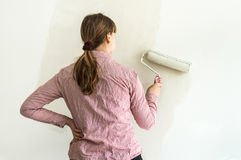 Painters colouring the wall with paint roller. Renovation or painting of interior with white color Royalty Free Stock Photo