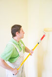 Painters and decoraters. Real painters and decorates during their work, painting the walls of the apartment and doing the repairs on the walls Royalty Free Stock Images