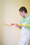 Painters and decoraters. Real painters and decorates during their work, painting the walls of the apartment and doing the repairs on the walls Royalty Free Stock Photos