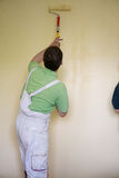 Painters and decoraters. Real painters and decorates during their work, painting the walls of the apartment and doing the repairs on the walls Royalty Free Stock Photography