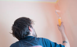 Painters and decoraters. Real painters and decorates during their work, painting the walls of the apartment and doing the repairs on the walls Stock Photo