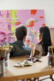 Painters In Discussion Over Painting Royalty Free Stock Photography