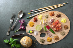 Painters food palette concept. Fresh seasoning cooking ingredients including herbs and spices on a painters palette Stock Photo