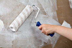 Painters hand holds paint roller, painting wall with white color Royalty Free Stock Images