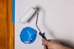 Painters hand with roller and masking blue tape Stock Photo