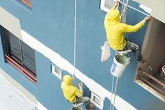 Painters hanging on roll, painting color on building wall. Young painting facade builder worker with roller brush, working on high building, working together royalty free stock photos