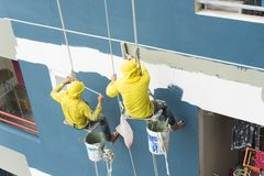 Painters hanging on roll, painting color on building wall. royalty free stock images
