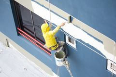Painters hanging on roll, painting color on building wall. Young painting facade builder worker with roller brush, working on high building, working together stock images