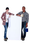 Painters holding an ad board Royalty Free Stock Images