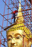 Painters are painting big golden Buddha statue. Painters are painting  big  golden Buddha statue under construction Stock Photo