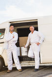 Painters smiling leaning against their van Royalty Free Stock Photos