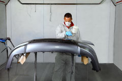 Painters use spray guns to apply paint to a bumper. Royalty Free Stock Image