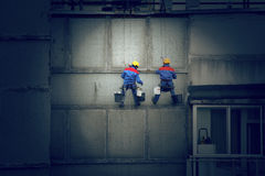 Painters on wall. Painters in hard hats and harnesses hanging high on concrete wall, working Royalty Free Stock Photography