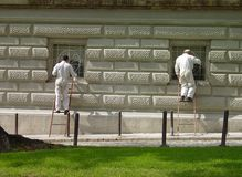 Painters at work. Two workers painting window bars on Belgrade's City Hall building stock image